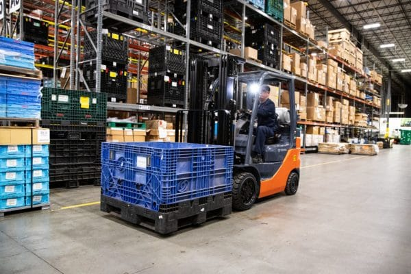 Toyota forklift carrying a load in warehouse