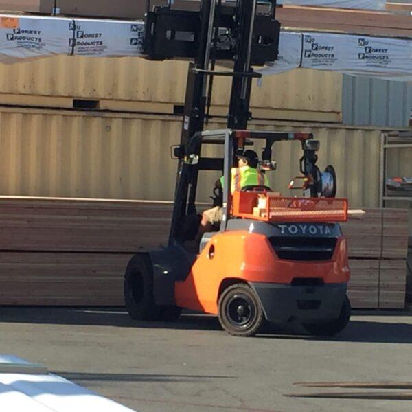 large toyota forklift lifting lumber