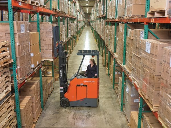 toyota stand up electric forklift loading pallet rack in warehouse