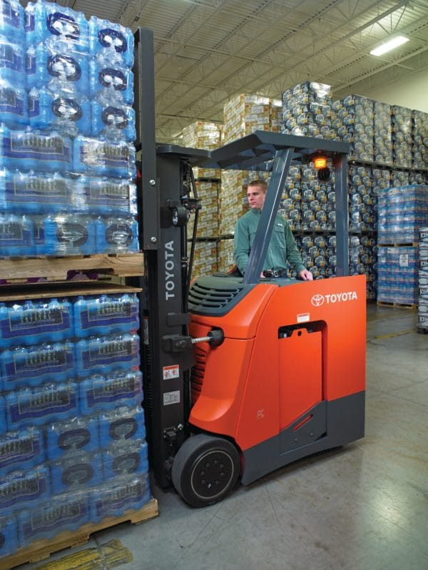 toyota stand up electric forklift lifting load in warehouse