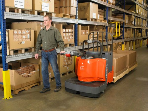 toyota end controlled rider pallet jack carrying load in warehouse